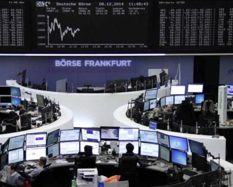 Traders are pictured at their desks in front of the german share price