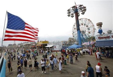 Beachgoers brave the high winds on the boardwalk at Coney Island, in New York, July 11, 2009. REUTERS/Chip East