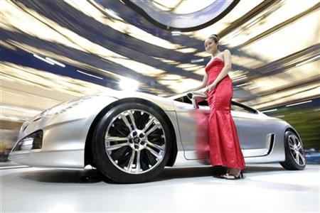 A model stands next to a Peugeot RC HYbrid4 car on display at the Shanghai International Auto show April 21, 2009. REUTERS/Aly Song