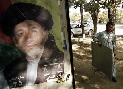 An Afghan man carries a sheet of iron next to a poster of President Hamid Karzai at his shop in Kabul September 12, 2009. REUTERS/Omar Sobhani
