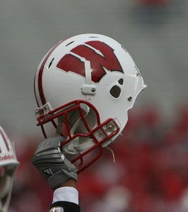 Wisconsin football player holds up a helmet during a football game. Taken by coach_connor2001 at Flickr. By CrdHwk at en.wikipedia (Transferred from en.wikipedia) [CC-BY-2.0 (http://creativecommons.org/licenses/by/2.0)], from Wikimedia Commons