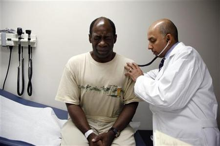 Ernest Sass, 52, (L) winces as he is attended to by Girish Bobby Kapur, M.D. (R) in a room used to see patients who don't require treatment for trauma inside the emergency room at Ben Taub General Hospital in Houston, Texas July 27, 2009. REUTERS/Jessica Rinaldi