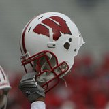 A Wisconsin football player holds up a helmet during a football game. Taken by coach_connor2001 at Flickr. By CrdHwk at en.wikipedia (Transferred from en.wikipedia) [CC-BY-2.0 (http://creativecommons.org/licenses/by/2.0)], from Wikimedia Commons