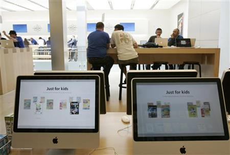 Customers look over Apple products at the company's retail store in San Francisco, California April 22, 2009. REUTERS/Robert Galbraith