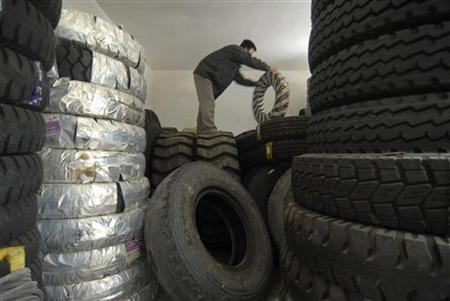 An employee moves tyres at a tyre shop in Baokang, Hubei province, September 12, 2009. REUTERS/Stringer