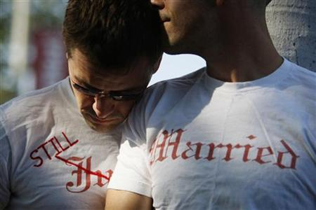 Gay couple Ethan Collings (L), 32, and his spouse Stephen Abate, 36, hug as they celebrate their one-year wedding anniversary in West Hollywood, California, June 16, 2009. REUTERS/Lucy Nicholson