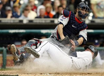 Minnesota Twins catcher Joe Mauer (top) tags out Detroit Tigers'Clete Thomas sliding into home-plate during the third inning of their MLB American League baseball game in Detroit, Michigan, September 29, 2009. REUTERS/Rebecca Cook