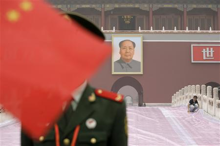 A worker covers the red carpet with a plastic sheet in front of Beijing's Tiananmen Gate September 30, 2009. REUTERS/Jason Lee