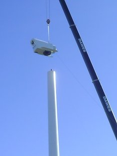 A crane installed the nacelee, or generator part, of a new 155-foot tall wind turbine at Wausau East High School.  The Northwind turbine will produce 100 kilowatts of electricity or about 5 percent of the school's electricity.  A second, smaller 15-kilowatt turbine will be installed in late October 2009.