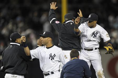 Robinson Cano (R) and Derek Jeter (2nd L) celebrate with team mates after the Yankees beat the Minnesota Twins during Game 1 of their MLB American League Division Series playoff baseball game in New York, October 7, 2009. REUTERS/Ray Stubblebine