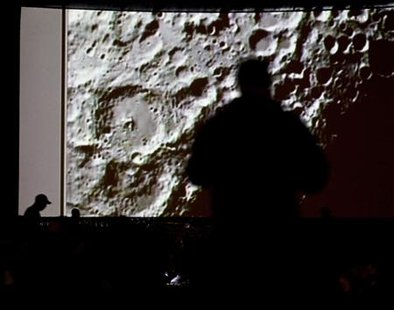 People watch a live video of the twin impacts of the Lunar Crater Observation and Sensing Satellite, or LCROSS, and its rocket's upper stage as they impact the moon at the NASA Ames Research Center in Moffett Field, California, October 9, 2009. REUTERS/Kim White