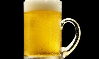A mug of golden beer with a white froth; against a black background. By Len Rizzi (photographer) [Public domain], via Wikimedia Commons