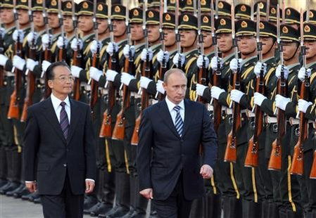 Russian Prime Minister Vladimir Putin (R) and Chinese Premier Wen Jiabao attend a welcoming ceremony at the Great Hall of the People in Beijing October 13, 2009. Russia and China looked to steady their close but increasingly imbalanced relationship on Tuesday when visiting Russian Prime Minister Vladimir Putin ushered through trade deals said to be worth $3.5 billion, including a framework agreement on the supply of Russian gas from state-ru