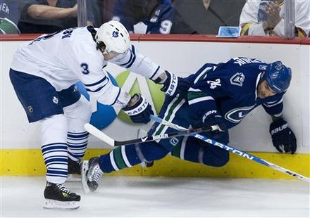 Toronto Maple Leafs Garnet Exelby (L) knocks down Vancouver Canucks Darcy Hordichuk during first period NHL hockey in Vancouver, British Columbia October 24, 2009. REUTERS/Andy Clark
