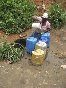 Khelina Sibuyi, 49, draws water from bore holes in the township of Mataffin, within sight of the new Mbombela World Cup stadium outside Nelspruit October 20, 2009. REUTERS/Barry Moody
