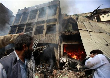 Men stand in front of a building after a bomb explosion in Peshawar, located in Pakistan's restive North West Frontier Province, October 28, 2009. REUTERS/Fayaz Aziz