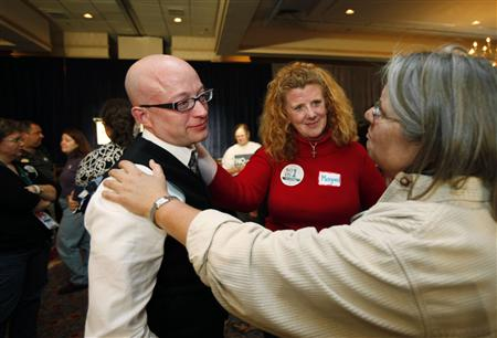 Gay marriage supporters Barb Wood (R) and Margaret O'Connell (C), comfort Tim Diehl as they wait for election results at the No on 1/Protect Maine Equality election night rally in Portland, Maine November 4, 2009. The group is working to prevent the repeal of Maine's gay marriage law, which was adopted last spring by Maine's legislature. REUTERS/Joel Page