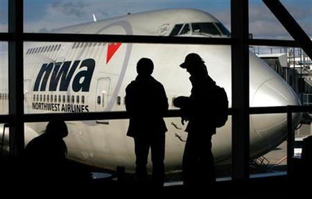 Passengers stand in front of a Northwest Airlines Boeing 747 at Detroit Metropolitan Wayne County Airport, February 6, 2006. REUTERS/John Gress
