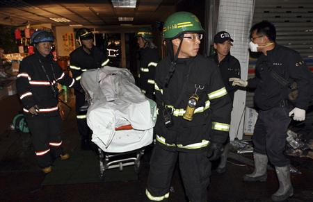 Firefighters evacuate the body of one of victims at the scene of a fire at an indoor shooting range in Busan, about 420 km (262 miles) southeast of Seoul November 14, 2009. REUTERS/Jo Jung-ho/Yonhap