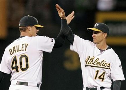Oakland Athletics Mark Ellis (R) slaps hands with Athletics' relief pitcher Andrew Bailey after their win over the New York Yankees during their MLB American League baseball game in Oakland, California August 17, 2009. REUTERS/Robert Galbraith