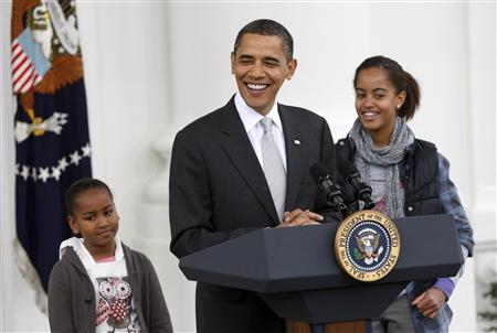 "U.S. President Barack Obama speaks alongside his daughters Sasha (L) and Malia, during a turkey pardoning ceremony for ""Courage"", the National Thanksgiving Turkey, on the North Portico of the White House in Washington, November 25, 2009. REUTERS/Jason Reed"