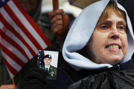 Joan Baxer of Ramsey, New Jersey holds a photograph of her son Sergeant Brian Baxer, 22, who has done two tours in Iraq and is awaiting deployment to Afghanistan, attends a rally against the plan to try those accused of plotting the 9/11 attacks at New York's Federal Court, in New York December 5, 2009. REUTERS/Finbarr O'Reilly