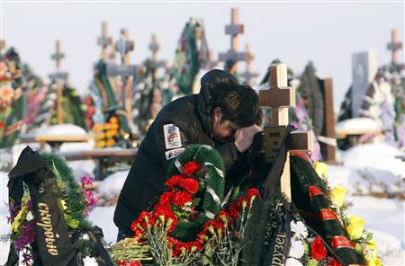 A friend of Timur Prokofiev, a victim of Friday's nightclub fire in Perm, grieves during his burial at a cemetery outside Perm, 1,150 km (720 miles) east of Moscow, December 6, 2009. REUTERS/Denis Sinyakov