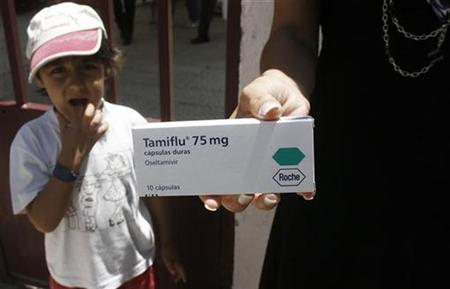 A boy looks at a woman holding out a box of Tamiflu as she talks with journalists outside a school in Lisbon July 7, 2009. REUTERS/Nacho Doce