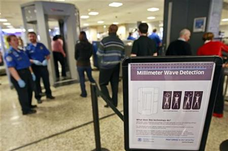 A sign explains the procedure for going through the whole body scan machine, or millimeter wave machine as passengers wait in line at a security check point at the Salt Lake International Airport in Salt Lake City, Utah, March 10, 2009. REUTERS/George Frey