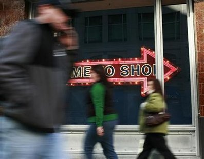 People walk past a sign during the holiday shopping season in San Francisco, California December 23, 2009. REUTERS/Robert Galbraith