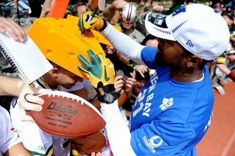 "Charles Woodson, a Green Bay Packers cornerback, signs a ""cheese head"" for Airman 1st Class Steve Ladwig, of the 8th Intelligence Squadron, during Pro Bowl practice at Earhart Field, Joint Base Pearl Harbor-Hickam, Hawaii, Jan. 26, 2012. By U.S. Air Force photo/Staff Sgt. Mike Meares [Public domain], via Wikimedia Commons"