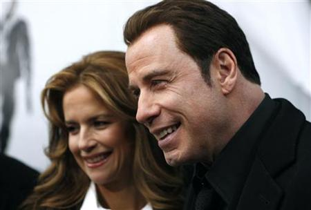 "Actor John Travolta (R) and his wife Kelly Preston speak to television reporters as they arrive at the premiere of ""From Paris With Love"" in New York January 28, 2010. REUTERS/Jessica Rinaldi"