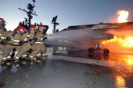 A repair locker hose team aboard USS John F. Kennedy (CV 67) combats a controlled fire on the mobile aircraft firefighting training device May 2, 2006. A crew of three Department of Defense firefighters travels with the simulator to train Kennedy's fire parties. Kennedy is under way conducting crew proficiency training off the coast of Florida. By Photographer's Mate 3rd Class Tommy Gilligan (http://jccc.afis.osd.mil/LBOX/full/1331173.jpg) [Public domain], via Wikimedia Commons