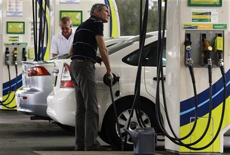 A man refuels his car at a petrol station in Sydney October 26, 2009. REUTERS/Daniel Munoz