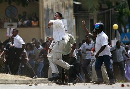 Supporters of former army commander General Sarath Fonseka throw rocks at supporters of President Mahinda Rajapaksa during a protest against Fonseka's arrest in Colombo February 10, 2010. REUTERS/Dinuka Liyanawatte