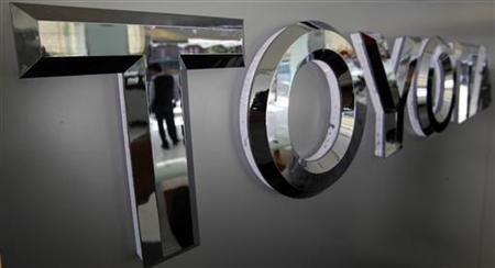 A man is reflected on a Toyota logo in a vehicle showroom in Taipei March 3, 2010. REUTERS/Nicky Loh