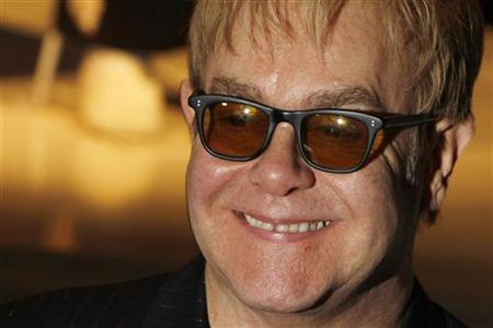 Singer songwriter Elton John poses for photographers as he opens charity store 'Out the Closet' in Covent Garden in London, December 11, 2009. REUTERS/Luke MacGregor