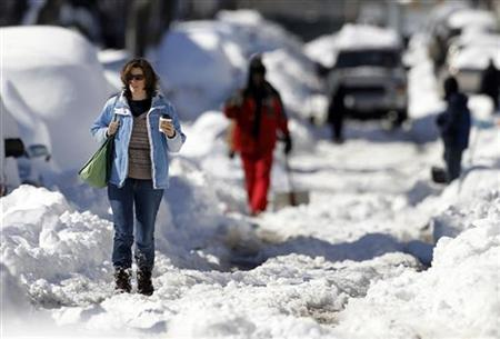 A woman walks through heavy snow as she carries her coffee on Capitol Hill in Washington, February 11, 2010. REUTERS/Jason Reed