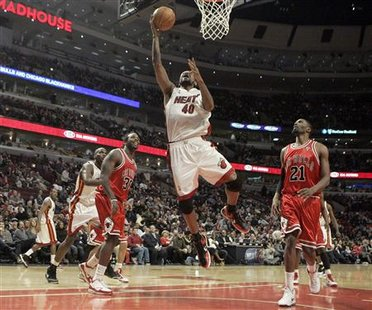 Miami Heat forward Udonis Haslem (C) drives to the basket between Chicago Bulls forwards Chris Richard (L) and Hakim Warrick in the fourth quarter of their NBA basketball game in Chicago, Illinois, March 25, 2010. REUTERS/Frank Polich