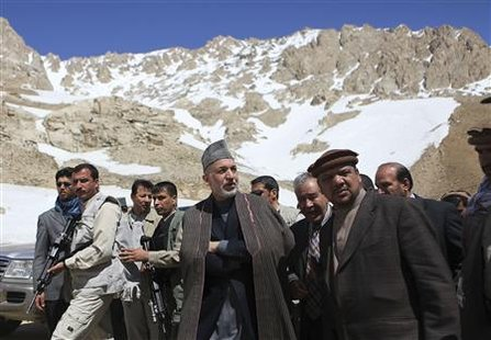 Afghan President Hamid Karzai (C) walks with his First Vice-President Muhammad Qasim Fahim (R) during their visit to the site of an avalanche at the Salang Pass, north of Kabul March 31, 2010. REUTERS/Rafiq Maqbool/Pool