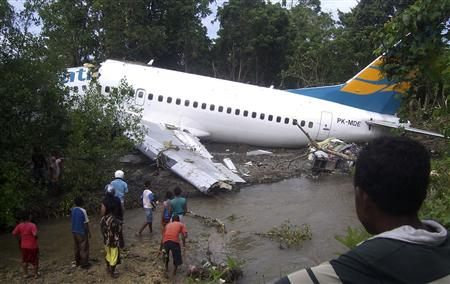 People gather to look at a Merpati Boeing 737-300 as it lies skidded off on the runway in Rendani airport in Manokwari of the Indonesia's West Papua province April 13, 2010. REUTERS/Laode Mursidin