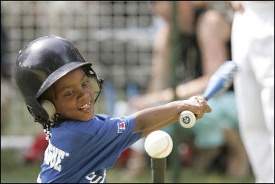 A young child plays in a game of tee-ball
