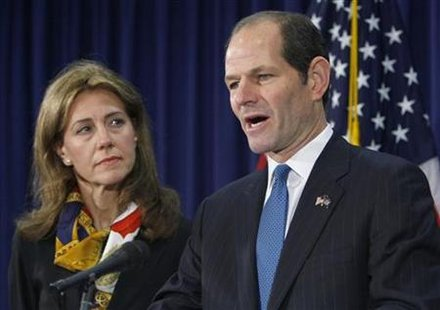New York Governor Eliot Spitzer (R) stands next to his wife Silda Wall Spitzer as he announces his resignation at his office in New York March 12, 2008. REUTERS/Brendan McDermid