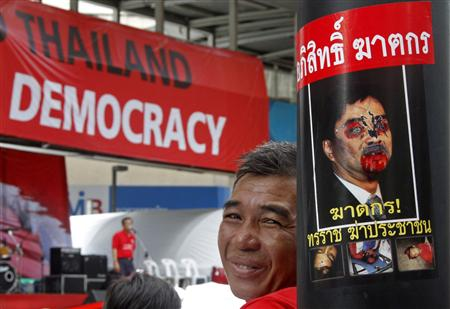 "An anti-government ""red shirt"" protester sits next to a defaced portrait of Thailand's Prime Minister Abhisit Vejjajiva in the main shopping district in Bangkok April 18, 2010. REUTERS/Eric Gaillard"
