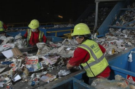 Workers help separate comingled recyclables at a single-stream recycling facility.