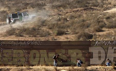 Immigrants hide from a border patrol vehicle while waiting a chance to cross into the United States at the border fence on the outskirts of the Tijuana, Mexico, September 19, 2009. REUTERS/Jorge Duenes