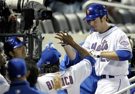 New York Mets batter Ike Davis (R) is congratulated at the dugout steps by teammates after he hit a home run against the Atlanta Braves in the fifth inning of their National League baseball game in New York April 23, 2010. REUTERS/Ray Stubblebine