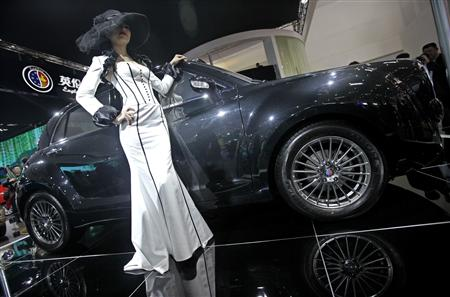 A model poses next to a Geely Englon TXN car at the Beijing Auto Show in Beijing April 23, 2010. REUTERS/Jason Lee