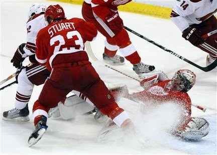 Detroit Red Wings goaltender Jimmy Howard (R) is sprayed with ice shavings while making a save against the Phoenix Coyotes in the second period of Game 6 of their NHL Western Conference quarter-final hockey game in Detroit, Michigan April 25, 2010. REUTERS/Rebecca Cook