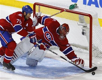 Montreal Canadiens goalie Jaroslav Halak and Hal Gill stop a loose puck during the first period of action against the Washington Capitals in Game 6 of their NHL Eastern Conference quarter-final series in Montreal, April 26, 2010. REUTERS/Shaun Best